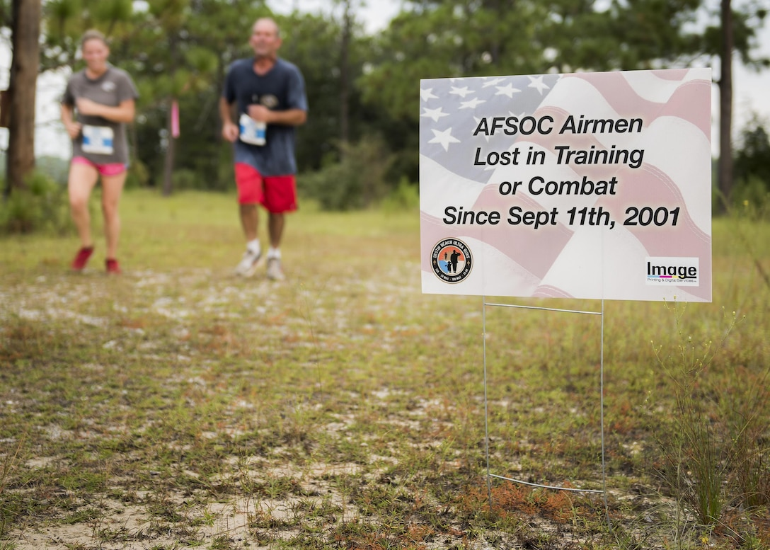 Runners move by a sign displaying the name of fallen Air Force special operator who lost his life after 9/11 during the Memorial 6k trail run Sept. 11 at Duke Field, Fla.  About 100 Airmen and families participated in the run.  (U.S. Air Force photo/Tech. Sgt. Sam King)