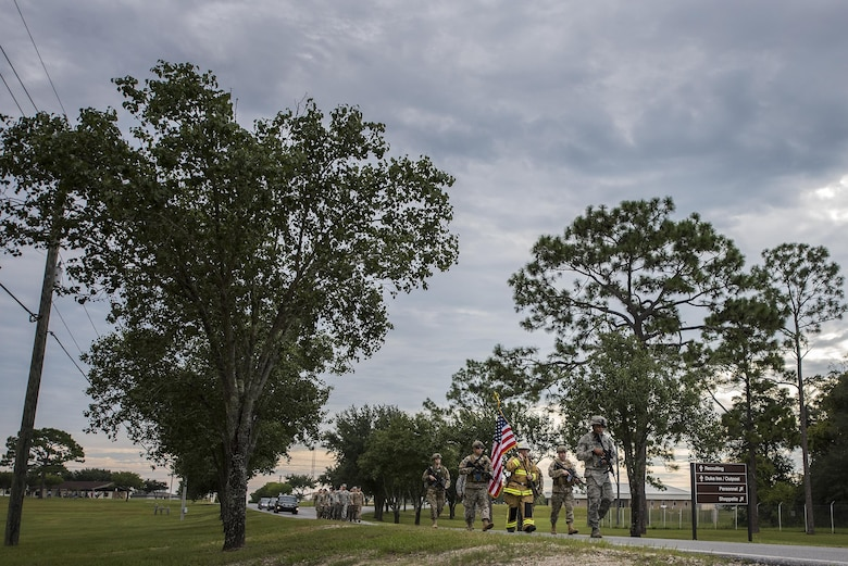 Chief Master Sgt. Pete Webb, 919th Special Operations Wing, carries a flag down the road toward the site of the unit's 9/11 Memorial Ceremony Sept. 11 at Duke Field, Fla.  The chief was escorted by wing security forces members.  The flag he carried was used during the 24-hour Memorial stair climb event that began the day before.  The stair climb event culminated in the delivery of the flag to the memorial ceremony. (U.S. Air Force photo/Tech. Sgt. Sam King)