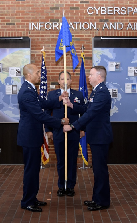 Lt. Col. Samuel McGlynn accepts the 42nd Cyberspace Operations Group guidon, assuming command of the squadron, from Col. Anthony M. Perkins, 960th Cyberspace Operations Group, as Chief Master Sgt. Mark Otzenberger, the squadron's new superintendent looks on, during a ceremony in the Ludwig Heritage Hall Atrium at Scott Air Force Base Sept. 12. The 42nd COS has a rich history, dating back to just after World War II when the 42nd Communications Squadron was first activated at Mitchell Air Force Base, New York, Nov. 17, 1949. (U.S. Air Force photo by Maj. Alysia R. Harvey)