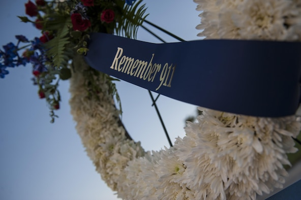 A wreath made to honor the victims of Sept. 11 hangs in front of the base flag pole, Sept. 9, 2016. To honor those Americans' sacrifices, Airmen from Nellis Air Force Base stood post from 6:30 a.m. to 4:30 p.m. in thirty minute shifts. (U.S. Air Force photo by Airman 1st Class Kevin Tanenbaum/Released)