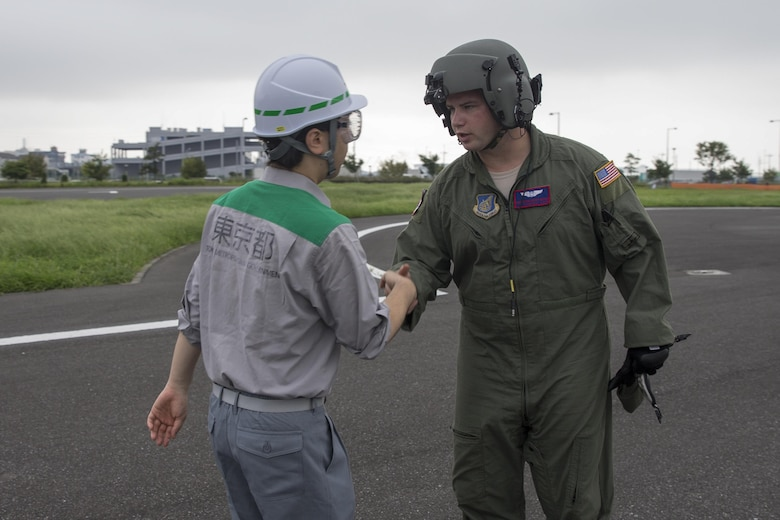 Tech. Sgt. Christopher Rector, 459th Airlift Squadron flight engineer, greets to a member with the Tokyo Metropolitan Government after landing the Tokyo Rinkai Disaster Prevention Park, Japan, Sept. 4, 2016, during the Annual Tokyo Metropolitan Government Disaster Management Drill. Airmen with the 459 AS practiced delivering simulated relief supplies to Tokyo Rinkai Disaster Prevention Park in downtown Tokyo. The park is located in the Ariake area and is a disaster countermeasure headquarters of the Government of Japan and other local governments during large-scale earthquakes in the metropolitan area. (U.S. Air Force photo by Yasuo Osakabe/Released)