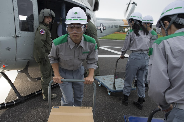 Members with the Tokyo Metropolitan Government pick up simulated relief supplies at Tokyo Rinkai Disaster Prevention Park, Japan, Sept. 4, 2016, during the Annual Tokyo Metropolitan Government Disaster Management Drill. Airmen with the 459 AS practiced delivering simulated relief supplies to Tokyo Rinkai Disaster Prevention Park in downtown Tokyo. The park is located in the Ariake area and is a disaster countermeasure headquarters of the Government of Japan and other local governments during large-scale earthquakes in the metropolitan area. (U.S. Air Force photo by Yasuo Osakabe/Released)