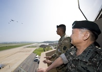 U.S. Army Gen. Vincent K. Brooks, U.S. Forces Korea commander, and Republic of Korea army Gen. Lee, Sun Jin, Chairman of the Republic of Korea Joint Chiefs of Staff, observe a U.S. Air Force B-1B Lancer escorted by ROK F-15K Slam Eagles performing a flyover over Osan Air Base, Republic of Korea, Sept. 13, 2016. Two U.S. Air Force B-1B Lancers from Andersen Air Force Base, Guam, were joined by Republic of Korean F-15K Slam Eagles and U.S. Air Force F-16 Fighting Falcons during the flyover. The close military cooperation between the U.S. and ROK keeps us ready to respond at any time to those who would threaten stability and security. (U.S. Air Force photo by Senior Airman Victor J. Caputo)