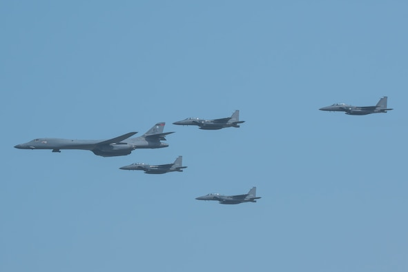 A U.S. Air Force B-1B Lancer, escorted by Republic of Korea air force F-15K Slam Eagles, performs a flyover over Osan Air Base, ROK, Sept. 13, 2016. The flyover highlighted the close cooperation between American and ROK military forces that keeps them ready to respond at any time to threats to stability and security. The B-1s are currently assigned to Andersen Air Force Base, Guam. (U.S. Air Force photo by Senior Airman Dillian Bamman)