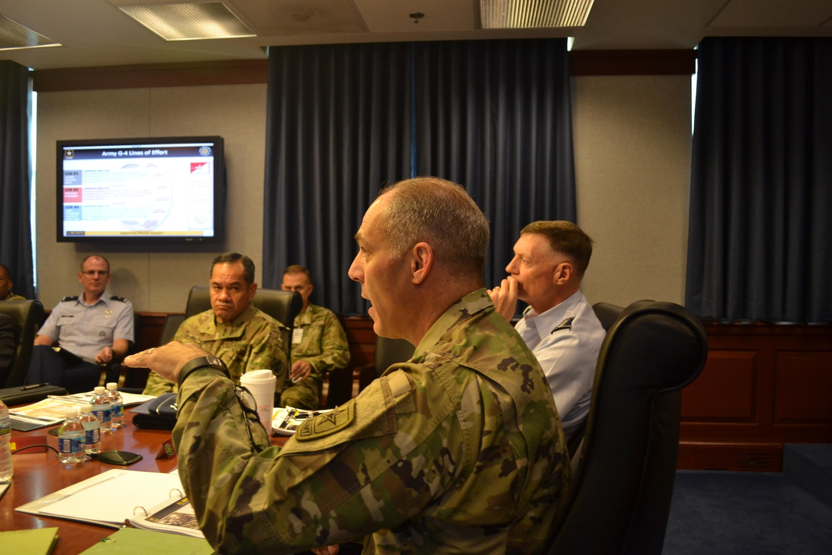 Army Lt. Gen. Gustave Perna (foreground) speaks at Army/DLA Day, Sept. 8 at the Pentagon, as (from far left) Air Force Brig. Gen. Martin Chapin, commander of DLA Energy, Army Command Sgt. Maj. Charles Tobin and Air Force Lt. Gen. Andy Busch listen.