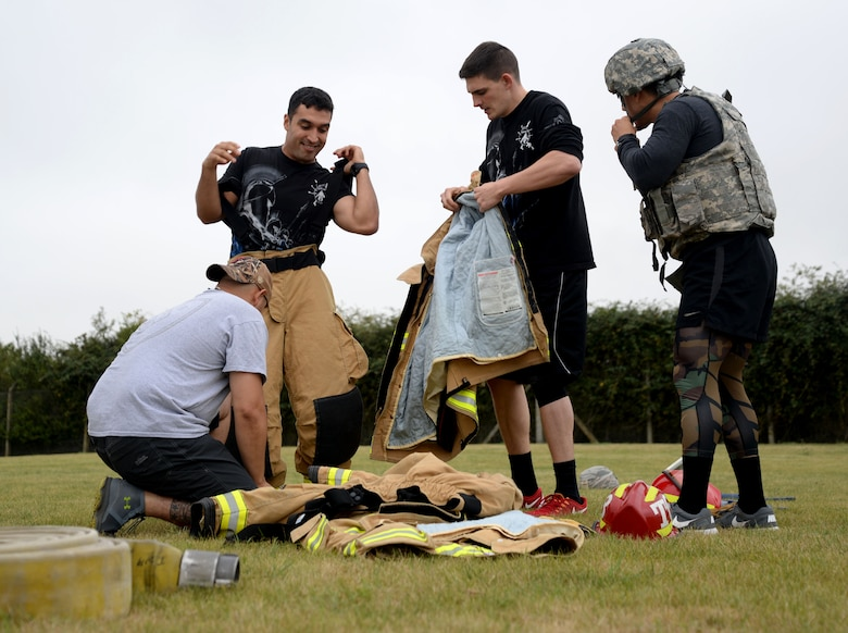 "A team of firefighters and defenders from the 48th Civil Engineer Squadron and the 48th Security Forces Squadron from RAF Lakenheath, scramble to get into each other's first-responder uniforms before performing various maneuvers Sept. 7, 2016, on RAF Mildenhall, England. RAF Mildenhall's team, comprising 100th CES firefighters and 100th SFS defenders, raced against their neighboring base counterparts during the ""Battle of the Badges."" The relay also involved a handcuffed M-16 assembly, a litter carry and a firehose challenge. (U.S. Air Force photo by Senior Airman Justine Rho)"