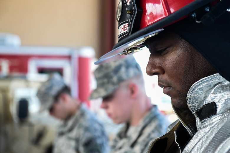 A member of Joint Task Force-Bravo's Fire Emergency Services bows his head with members of the Medical Element and Joint Security Forces during the 9/11 remembrance ceremony at Soto Cano Air Base, Honduras, Sept. 9, 2016. Throughout the ceremony, members of the three emergency services agencies stood together as sign of solidarity and as a way to honor their fallen colleagues