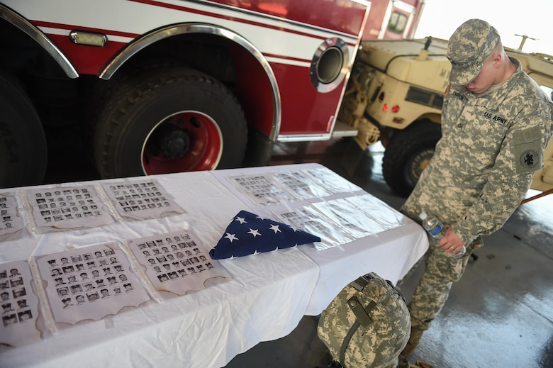 A member of Joint Task Force-Bravo looks at the emergency services monument set up for the 9/11 remembrance ceremony at Soto Cano Air Base, Honduras, Sept. 9, 2016. Pictures of the 447 first responders who lost their lives during the terrorist attacks of Sept. 11, 2001 were displayed on the monument.