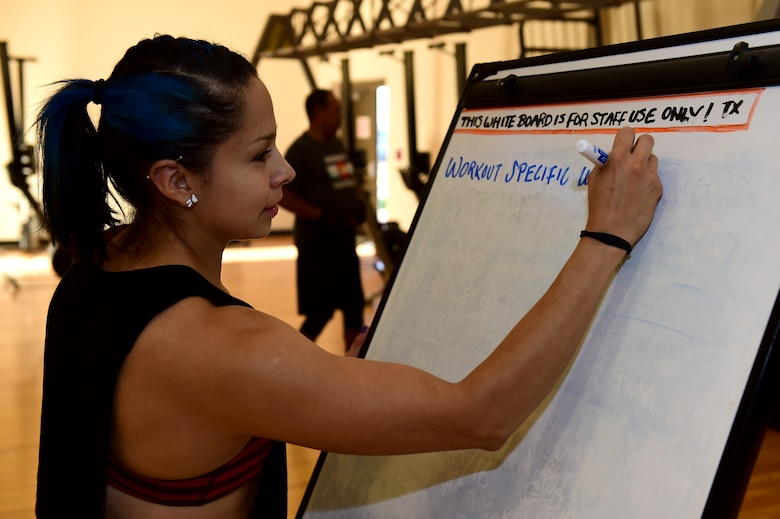 Azul Farrera, 460th Force Support Squadron recreation assistant, writes a workout plan for her class Sept. 9, 2016, at the Buckley Fitness Center on Buckley Air Force Base, Colo. The fitness center provides personal training at no cost to active duty service members. (U.S. Air Force photo by Airman 1st Class Gabrielle Spradling/Released)