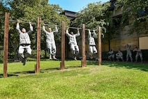Four Airmen assigned to the 4th Security Forces Squadron perform pullups as part of a 10-minute exercise warm-up, Sept. 9, 2016, at Seymour Johnson Air Force Base, North Carolina. Airmen from the 4th SFS were selected to complete a seven-day training program to become certified combative basic instructors. (U.S. Air Force photo by Airman Shawna L. Keyes)