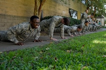 Airmen from the 4th Security Forces Squadron do push-ups and squats during an exercise warm-up, Sept. 9, 2016, at Seymour Johnson Air Force Base, North Carolina. Airmen did different exercises during a 10-minute warm-up as part of combative training. (U.S. Air Force photo by Airman Shawna L. Keyes)