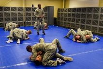 Tech. Sgt. Franklin Mosley (standing), 633rd Security Forces Squadron combative training instructor, teaches a group of defenders from the 4th SFS, Sept. 9, 2016, at Seymour Johnson Air Force Base, North Carolina. Airmen completed seven 10-hour days of instruction in combative training to become certified basic instructors. (U.S. Air Force photo by Airman Shawna L. Keyes)
