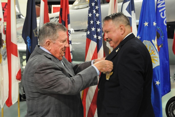 """Retired Maj. Gen. Richard Secord places the retirement pin on Dr. Charles """"Doc"""" Merkel during a ceremony Aug. 30, at the Air Force Armament Museum on Eglin Air Force Base, Fla. Merkel served at the 53rd Wing historian from 2007 to 2016."""
