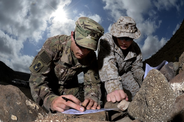 U.S. Army Cpl. Gregory McLellan and U.S. Marine Corps Cpl. Clinton Smith plot grid points during a joint training exercise at Arta, Djibouti. Through informal methods like training exercises, as well as formally established joint forums, the services  work together to share new technology and ideas to develop, test and deliver ever-better capabilities for Marines and Soldiers.  (U.S. Air Force photo by Tech. Sgt. Dan DeCook)