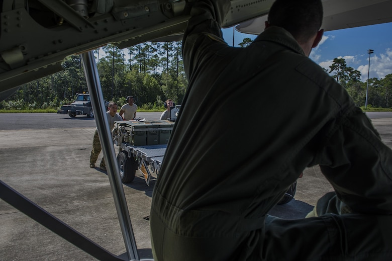 Staff Sgt. Oscar Garcia, an aerial gunner with the 1st Special Operations Group Detachment 2, watches as munitions systems specialists with the 1st Special Operations Aircraft Maintenance Squadron bring 30 mm rounds to be loaded onto an AC-130J Ghostrider gunship at Hurlburt Field, Fla., Sept. 6, 2016. The AC-130J is modified with the Precision Strike Package, which includes a mission management console, robust communications suite, two electro-optical/infrared sensors, advanced fire control equipment, precision guided munitions delivery capability as well as trainable 30mm and 105mm weapons. (U.S. Air Force photo by Airman 1st Class Isaac O. Guest IV)