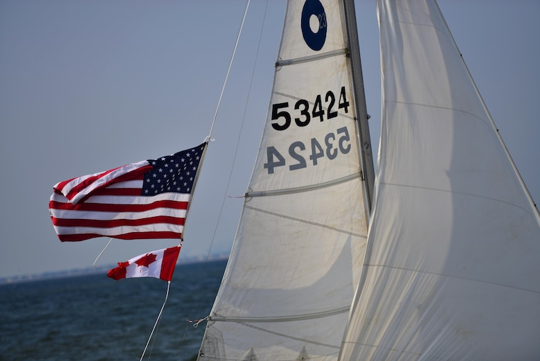 An American flag flies with a Canadian flag aboard a sailboat during the Tri-Services Regatta on the Chesapeake Bay, Va., Sept. 11, 2016. The Tri-Services Regatta is held by different military-affiliated yacht clubs each year, this year the race was held to support the 15th anniversary of 9/11.  (U.S. Air Force photo by Airman 1st Class Tristan Biese)
