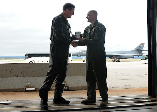 Col. Bradley Cochran, vice commander assigned to the 28th Bomb Wing, presents a token of appreciation to Air Commodore Theodorus ten Haaf, the defense attaché representing the Netherlands, during a presentation of B-1 bomber capabilities at Ellsworth Air Force Base, S.D., Sept. 12, 2016. The event concluded a visit by military attachés from throughout the world who stopped at Ellsworth as the first location in a multi-state tour. (U.S. Air Force photo by Airman 1st Class Marshall L. Brown)