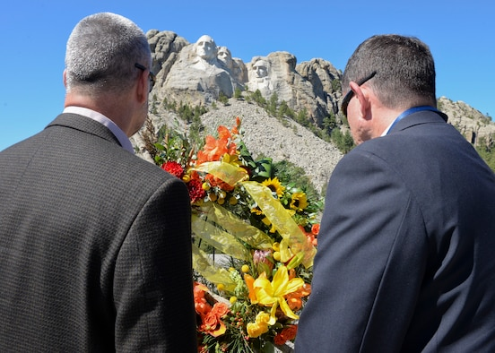 Rear Admiral William Truelove, Canadian Navy, and John A. Atela, director of the Office of Partner Engagement, stand in silence at the Mount Rushmore National Memorial, S.D., Sept. 11, 2016, to honor the 15th anniversary of the attacks on Sept. 11, 2001. A wreath laying ceremony was conducted by senior foreign and U.S. attachés on behalf of the Foreign Defense Attaché Corps, an organization based in Washington D.C., and made up of more than 120 nations. (U.S. Air Force photo by Senior Airman Anania Tekurio)