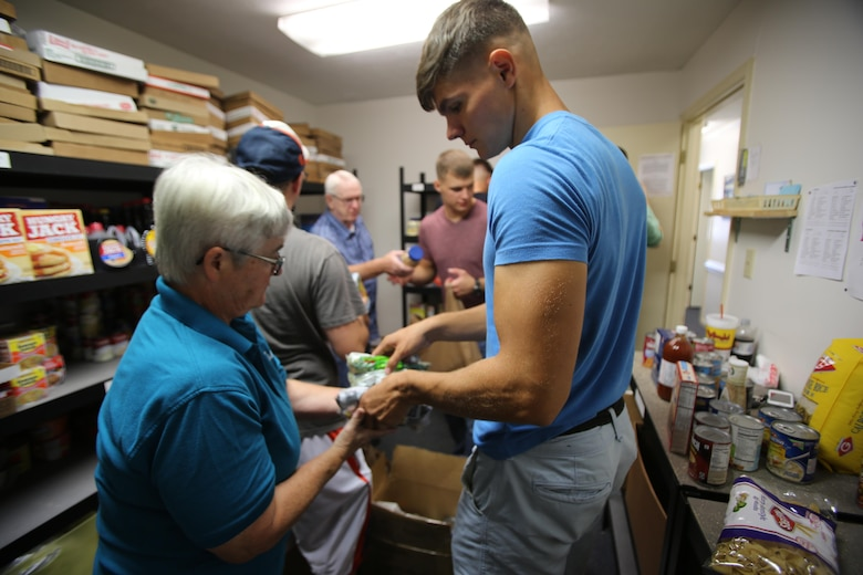 Trina Charles, left, and Lance Cpl. Stuart Dunlap pass nonperishable food items for shelf stocking during the U.S. Department of Agriculture's annual Feds Feed Families food drive at the Havelock Cherry Point Ministerial Association in Havelock, N.C., Sept. 7, 2016. Launched in 2009 as part of President Barack Obama's United We Serve campaign, the nationwide drive has collected over 52 million pounds of nonperishable food items for people struggling to put food on their table. MCAS Cherry Point personnel were responsible for donating 26,805 pounds of nonperishable food items. Charles is a volunteer with the HCPMA, and Dunlap is a refrigeration and air conditioning technician with Marine Wing Communications Squadron 28, Marine Air Control Group 28, 2nd Marine Aircraft Wing. (U.S. Marine Corps photo by Cpl. Jason Jimenez/Released)