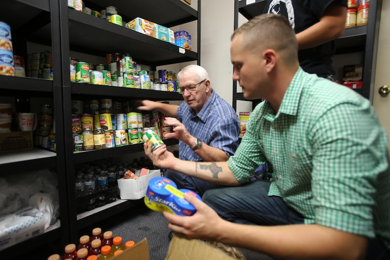 Billy Charles, left, and Cpl. Jacob Williamson pass nonperishable food items for shelf stocking during the U.S. Department of Agriculture's annual Feds Feed Families food drive at the Havelock Cherry Point Ministerial Association in Havelock, N.C., Sept. 7, 2016. Launched in 2009 as part of President Barack Obama's United We Serve campaign, the nationwide drive has collected over 52 million pounds of nonperishable food items for people struggling to put food on their table. MCAS Cherry Point personnel were responsible for donating 26,805 pounds of nonperishable food items. Charles is a volunteer with the HCPMA and Williamson is a Tropospheric Scatter Microwave Radio Terminal 170 operator with Marine Wing Communications Squadron 28, Marine Air Control Group 28, 2nd Marine Aircraft Wing. (U.S. Marine Corps photo by Cpl. Jason Jimenez/Released)