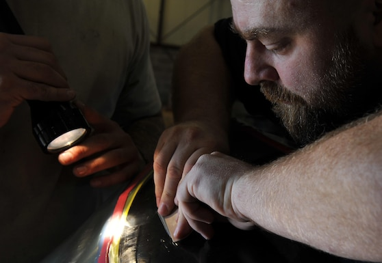 Kevin Wagers, 19th Maintenance Squadron propulsions craftsman, removes air bubbles from a polyurethane patch on a propeller blade's surface Sept. 8, 2016, in the C-130 Propulsions shop at Little Rock Air Force Base, Ark. The patch is a protective coating for the carbon fiber blade. (U.S. Air Force photo by Kevin Sommer Giron)