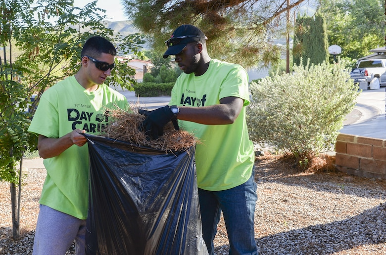 Airmen 1st Class Michael and Michael, Day of Caring volunteers, who are both heating, ventilation and air conditioning technicians with the 49th Civil Engineer Squadron here, gather pine needles from a disabled resident's front lawn in Alamogordo, N.M. on Sept. 9, 2016. The annual Day of Caring volunteer event helps disabled individuals and senior citizens within the Otero County community. (Last names are being withheld due to operational requirements. U.S. Air Force photo by Airman Alexis P. Docherty)
