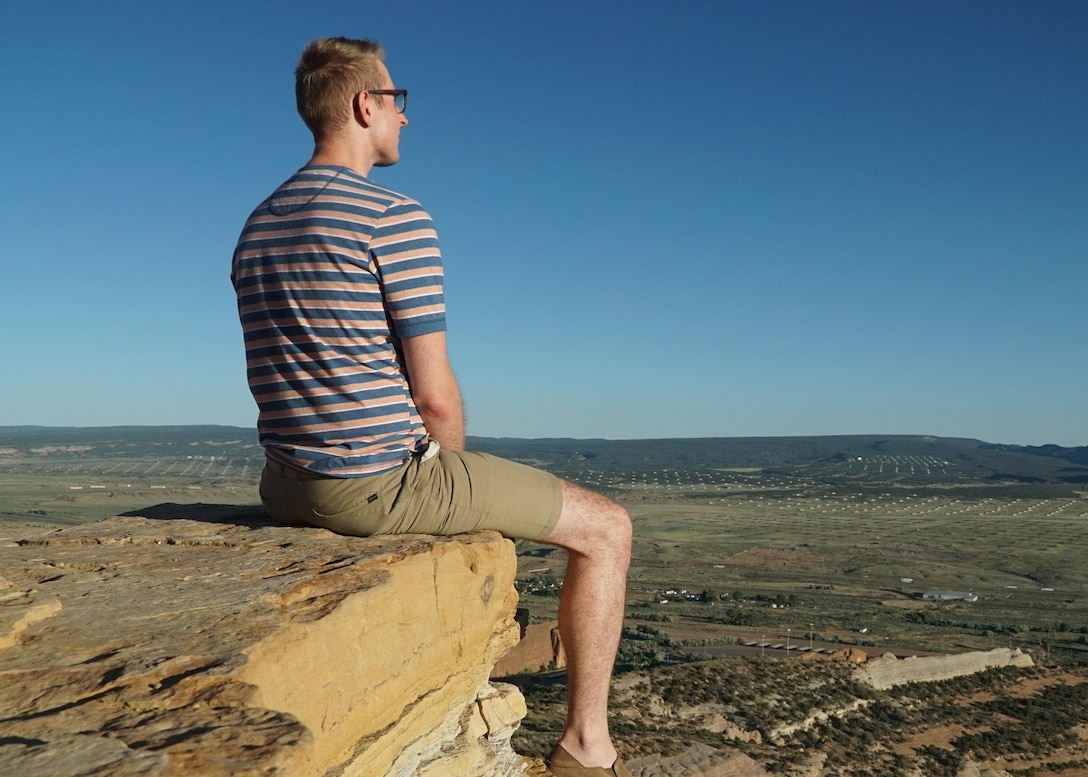 Senior Airman Troy Serad, an engineering assistant with the 446th Civil Engineer Squadron, sits near the edge of a cliff after hiking to Pyramid Rock June 14, 2016, near Gallup, N.M. During Serad's 10th grade year of high school he was homeless and dropped out of school. Serad eventually went back to school and is currently studying for the entrance exam to law school. (U.S. Air Force Reserve photo by Tech. Sgt. Bryan Hull)