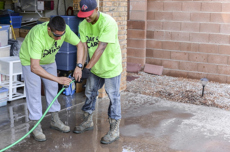 Airmen 1st Class Michael and Shawndell, Day of Caring volunteers, who are both heating, ventilation and air conditioning technicians with the 49th Civil Engineer Squadron here, fix a disabled resident's faulty watering hose in Alamogordo, N.M. on Sept. 9, 2016. Hundreds of Holloman Airmen volunteered for the 25th annual Day of Caring. (Last names are being withheld due to operational requirements. U.S. Air Force photo by Airman Alexis P. Docherty)