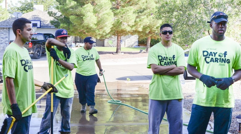 Members of the 49th Civil Engineer Squadron team up to beautify a disabled resident's front lawn and backyard as part of the annual Day of Caring volunteer event in Alamogordo, N.M. on Sept. 9, 2016. Hollomen Airmen account for a majority of the Day of Caring volunteer event taskforce. (U.S. Air Force photo by Airman Alexis P. Docherty)
