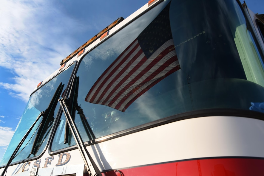 """PETERSON AIR FORCE BASE, Colo. -  A reflection of the American Flag bounces off the windshield of a fire engine assigned to the Colorado Springs Fire Department during the 9/11 Remembrance Ceremony at Peterson Air Force Base, Colo., Sept. 11, 2016. The ceremony paid respect to the lives lost in the terrorist attacks of 9/11 with the ringing of the """"four fives,"""" a salute volley, presentation of wreaths and the playing of taps. (U.S. Air Force photo by Airman 1st Class Dennis Hoffman)"""