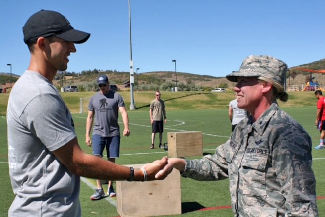 Brig. Gen. Christine Burckle, Utah Air National Guard Commander, presents a personal coin to Kevin Williams, brother of fallen Green Beret Sgt. 1st Class Matthew McClintock, who was killed saving an Airman teammate on Jan. 5 in Afghanistan. Burckle gave remarks at a fitness event on Sept. 10 in Park City, Utah, honoring McClintock, who was awarded the Silver Star for his actions in combat. McClintock was part of the 19th Special Forces Group, which is headquartered in Utah.
