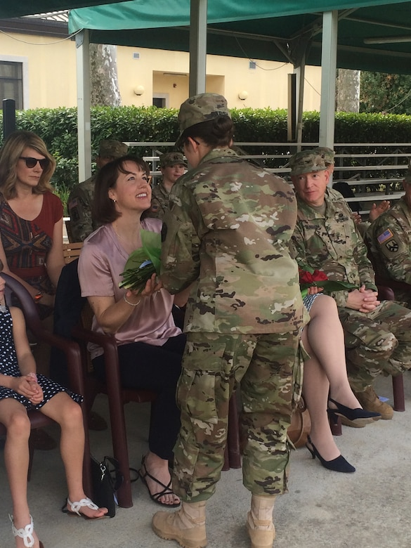 Laura Varhola is presented with a bouquet of yellow flowers to welcome her into the 2500th Digital Liasion Detachment during a ceremony Sunday, September 11, 2016 at Hoekstra Field, on Caserma Ederle in Vicenza, Italy. Her husband,  Col. Christopher Varhola, took command of the 2500th Digital Liaison Detachment from Col. David Mundfrom. Brig. Gen. Steven W. Ainsworth, the commanding general of the 7th Mission Support Command, presided over the ceremony, passing the unit's guideon from the outgoing to the incoming commander. (Photos by 1st Lt. Julie McCabe)