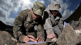 U.S. Army Cpl. Gregory McLellan and U.S. Marine Corps Cpl. Clinton Smith, Joint Corporals Leadership Development Course students, plot grid points during the land navigation portion of Camp Lemonnier's Joint Corporal's Leadership Development Course at Arta, Djibouti, March 3, 2016. During the evaluation ‎Soldiers, ‎Sailors, ‎Airmen, and ‎Marines had to find eight different points and navigate to those points in a timed event.