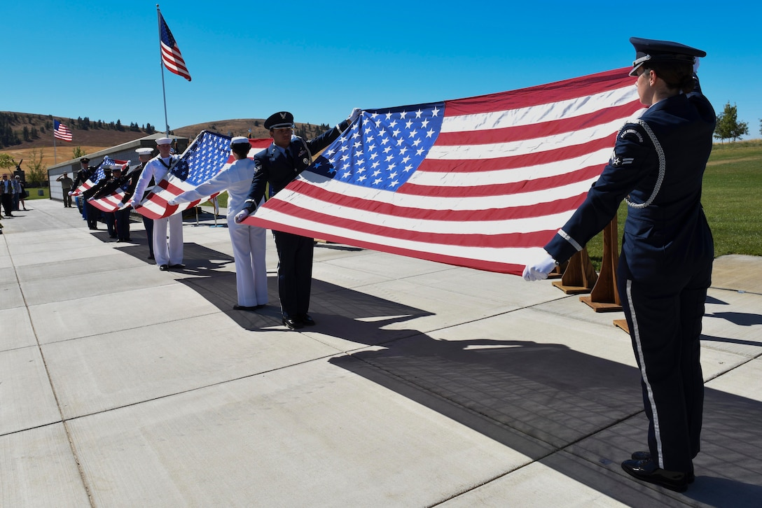 Fairchild Air Force Base honor guard presents the American Flag alongside the Air Force's sister services during the Missing in America Interment Service Sept. 13, 2016, at Washington State Cemetery at Medical Lake, Washington. More than 60 veterans were interred during the ceremony. (U.S. Air Force photo/Senior Airman Nick J. Daniello)