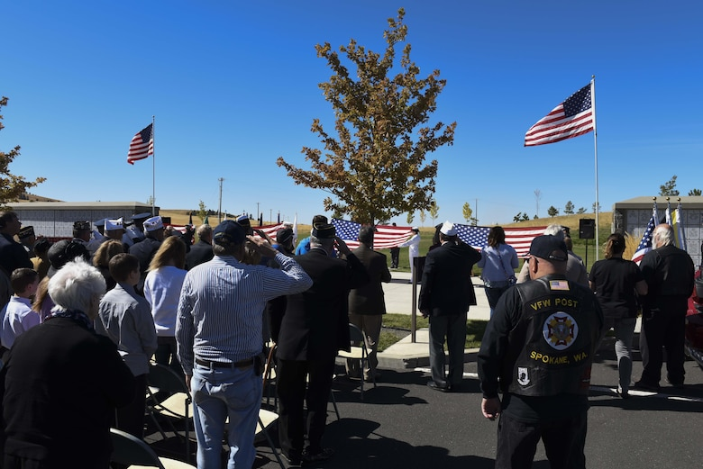 Attendees salute during the presentation of the American Flag during the Missing in America Interment Service Sept. 13, 2016, at Washington State Cemetery at Medical Lake, Washington. Over 100 people attended the ceremony to witness the veterans interred. (U.S. Air Force photo/Senior Airman Nick J. Daniello)