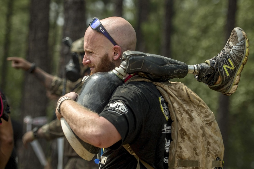 A member of Operation Enduring Warrior carries a teammate's prosthetic leg as they move from one obstacle to another during a Spartan Sprint Race at Fort Bragg, N.C..