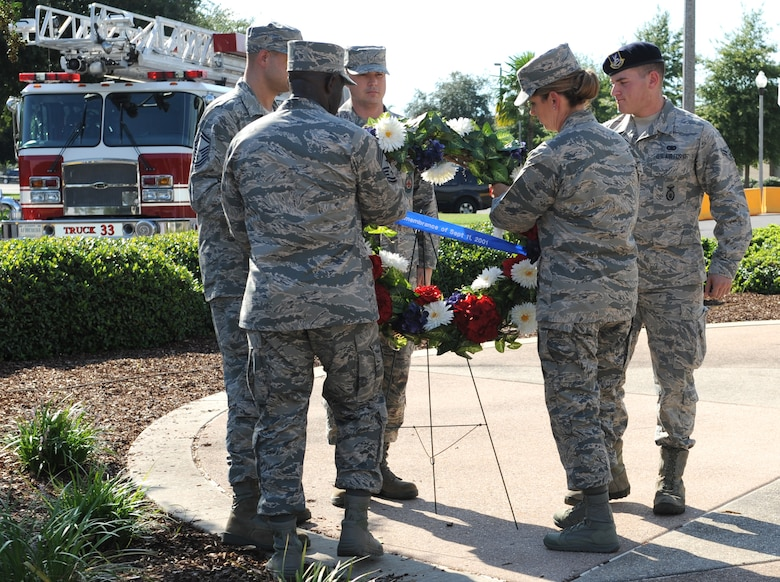 Col. Michele Edmondson, 81st Training Wing commander, Chief Master Sgt. Vegas Clark, 81st TRW command chief, and Keesler emergency rescue members place a wreath on display during a 9/11 memorial ceremony, Sept. 12, 2016, on Keesler Air Force Base, Miss. Fifteen years ago on Sept. 11, 2001, 19 terrorists simultaneously hijacked four passenger jets; flying one into the Pentagon in Washington, D.C., two into the World Trade Center in New York City, New York and one crashing outside of Shanksville, Pa. A total of 2,996 people were killed in the attacks.  (U.S. Air Force photo by Kemberly Groue/Released)