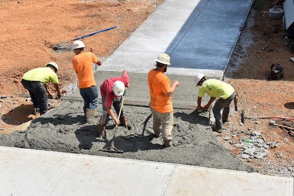 Workers connect a walkway with poured, wet cement Sept. 14, 2016, between the new facility and the older dormitory buildings on campus at the I.G. Brown Training and Education Center on McGhee Tyson Air National Guard Base in Louisville, Tenn. (U.S. Air National Guard photo by Master Sgt. Mike R. Smith/Released)