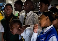 South African students anxiously wait to sit in the cockpit of a C-17 Globemaster III at the African Aerospace and Defense Expo at Waterkloof Air Force Base, South Africa, Sept. 14, 2016. The U.S. military is exhibiting a C-17 Globemaster III, a KC-135 Stratotanker, a C-130J Super Hercules, an HC-130 King, and an MQ-9 Reaper. The aircraft come from various Air National Guard and Air Force Reserve Command units. The U.S. routinely participates in events like AADE to strengthen partnerships with regional partners. (U.S. Air Force photo by Tech. Sgt. Ryan Crane)