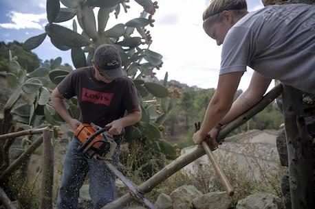 Lance Cpl. Raymond Dillworth, a combat engineer with Special Purpose Marine Air-Ground Task Force Crisis Response-Africa, shortens a fence post with a chainsaw in Vizzini, Sicily, Sept. 7, 2016.  Marines volunteered to clean up a local historic site and build fences during a community relations project.  (U.S. Marine Corps photo by Cpl. Alexander Mitchell/released)