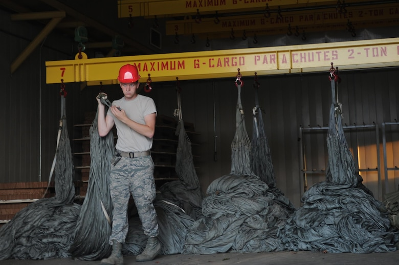 U.S Air Force Senior Airman Addison Schneider, 19th Logistics Readiness Squadron Aerial Delivery element member, removes a parachute Aug. 29, 2016, at Hangar 259 on Little Rock Air Force Base, Ark. Cargo platform parachutes are required to hang in a heated room for at least 72 hours to ensure they are completely dry.