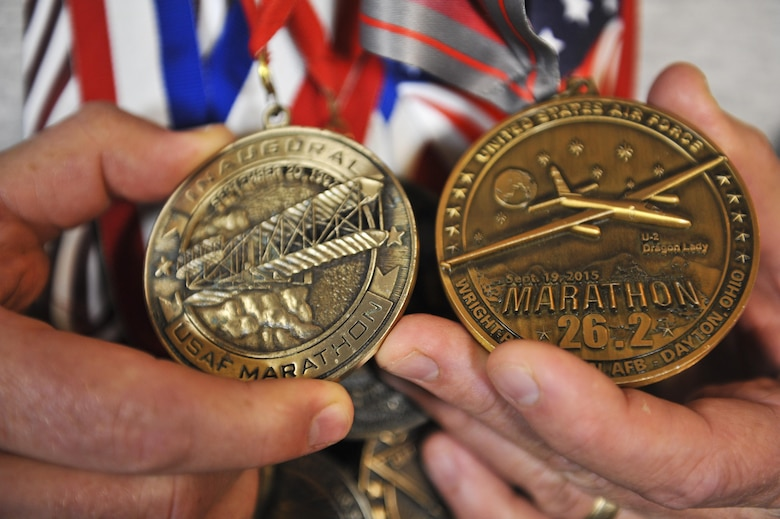 Master Sgt. Brian, 22nd Intelligence Squadron, holds his first and last U.S. Air Force Marathon medals, September 9, 2016 at Fort Meade, Md. Brian is the last active-duty Airman to compete in all 19 USAF Marathons to date and is competing in the 20th USAF Marathon on September 17, 2016 at Wright-Patterson Air Force Base, Ohio. (U.S. Air Force photo/Staff Sgt. AJ Hyatt)