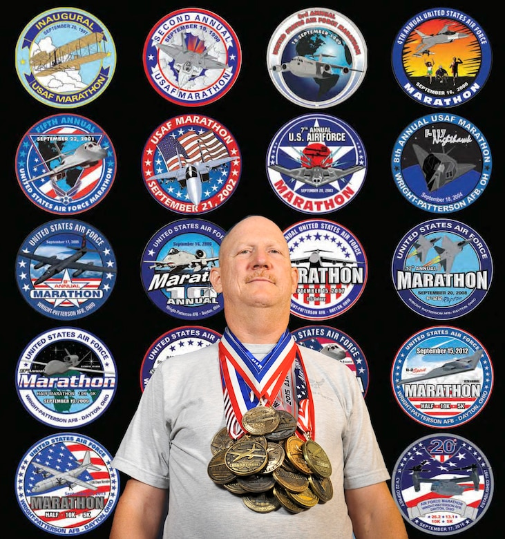Master Sgt. Brian, 22nd Intelligence Squadron, poses with all 19 of his U.S. Air Force Marathon medals, September 9, 2016 at Fort Meade, Md. Brian is the last active-duty Airman to compete in all 19 Air Force Marathons to date and is competing in the 20th Air Force Marathon on September 17, 2016 at Wright-Patterson Air Force Base, Ohio. (U.S. Air Force photo illustration/Staff Sgt. AJ Hyatt)