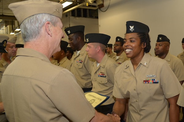 Engineman 1st Class Staci Allen shakes hands with Vice Adm. Tom Moore prior to receiving her Navy Afloat Maintenance Training Strategy (NAMTS) Certificate of Completion. Allen is a Sailor attached to Southeast Regional Maintenance Center (SERMC) in Mayport, Fla.
