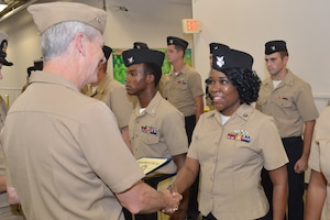Damage Controlman 1st Class Fungai Diura shakes hands with Vice Adm. Tom Moore prior to receiving her Navy Afloat Maintenance Training Strategy (NAMTS) Certificate of Completion. Diura is a Sailor attached to Southeast Regional Maintenance Center (SERMC) in Mayport, Fla.