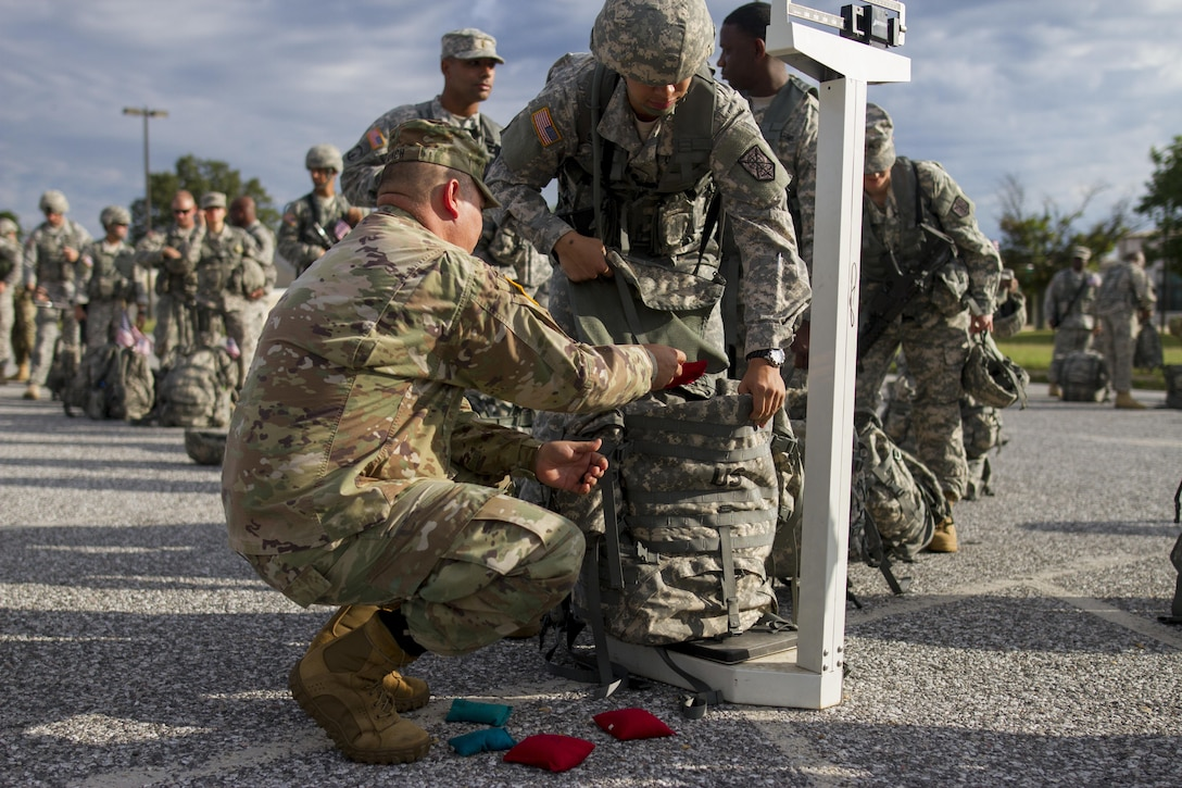 U.S. Army Reserve Soldiers assigned to the 200th Military Police Command weight their ruck sacks prior to a ruck march on Fort Meade, Md., Sept. 11, 2016. The Soldiers marched five miles with 35-pound ruck sacks. Before starting the march, the unit conducted a moment of silence in honor of those lost during 9/11 and Soldiers shared their personal memories of the attacks. (U.S. Army Reserve photo by Spc. Stephanie Ramirez)