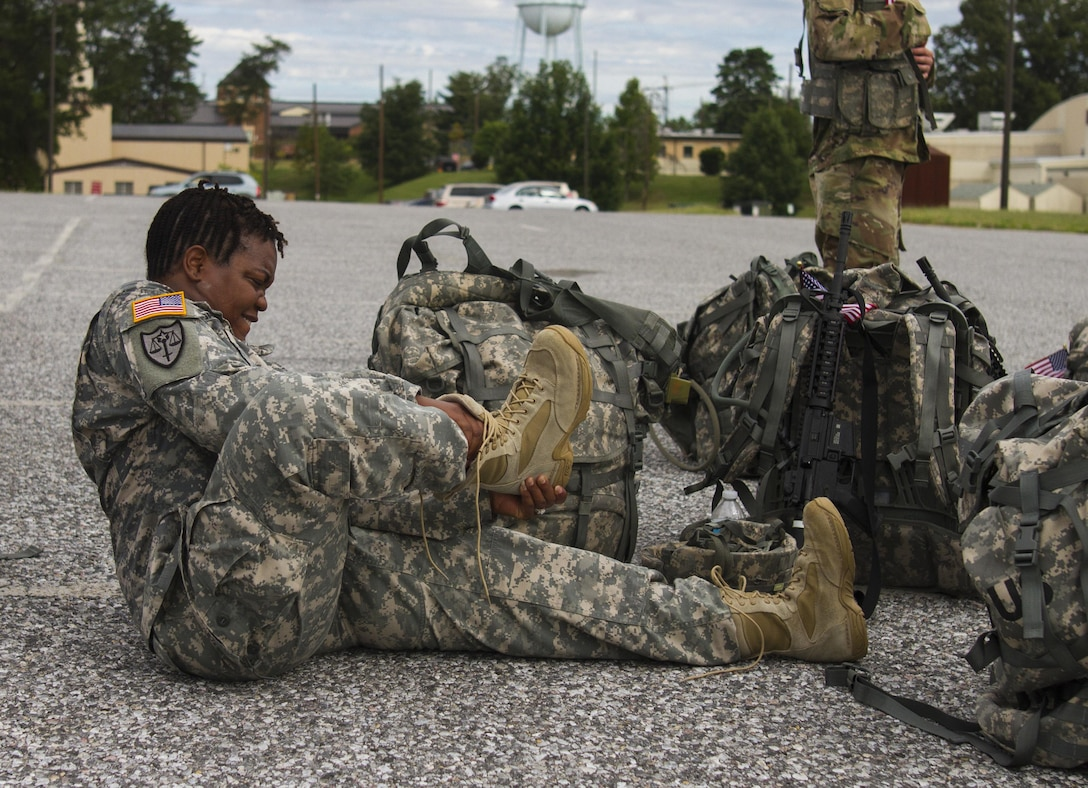 A U.S. Army Reserve Soldier assigned to the 200th Military Police Command removes her combat boots after a ruck march on Fort Meade, Md., Sept. 11, 2016. The Soldiers marched five miles with 35-pound ruck sacks. Before starting the march, the unit conducted a moment of silence in honor of those lost during 9/11 and Soldiers shared their personal memories of the attacks. (U.S. Army Reserve photo by Spc. Stephanie Ramirez)