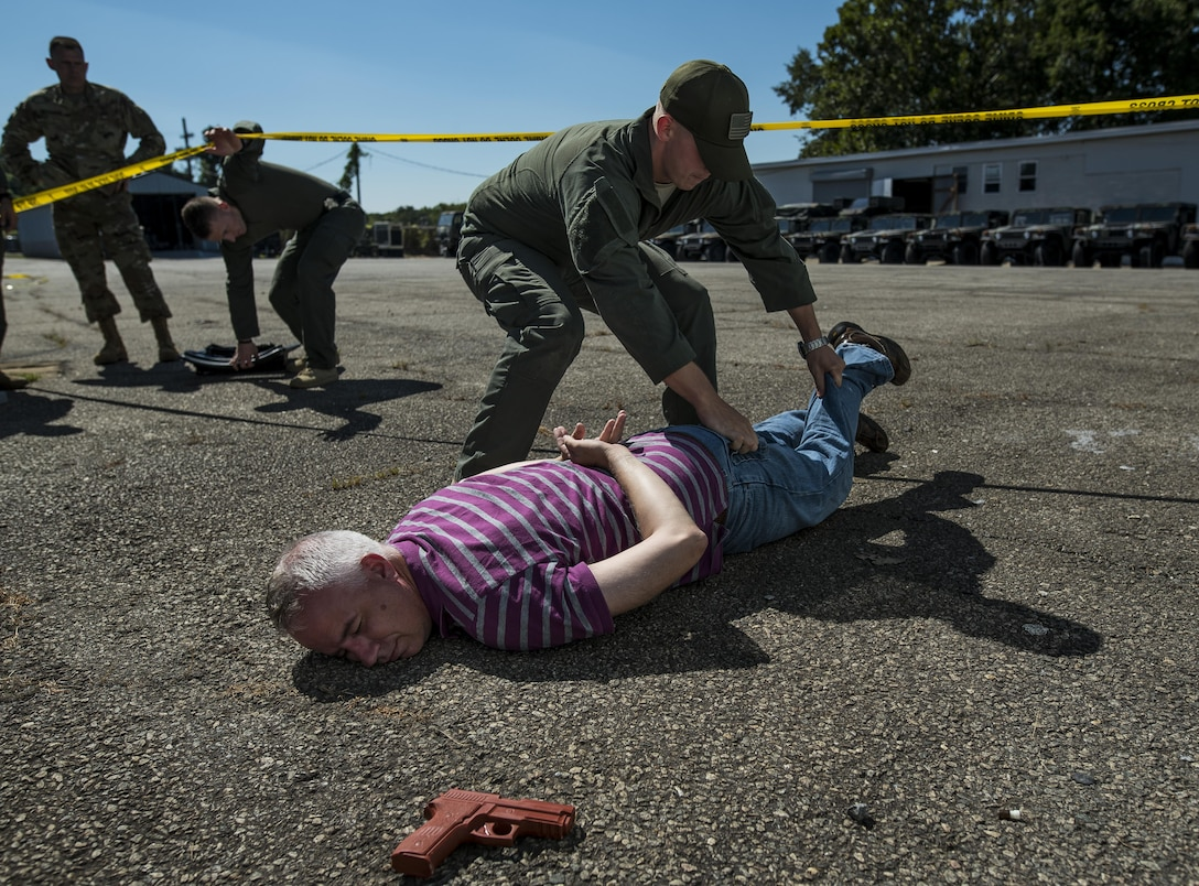 A member of the Special Reaction Team, Military District of Washington, inspects 1st Sgt. Donald Rackley, senior enlisted leader of the 733rd Military Police Battalion (Criminal Investigation Division), who pretended to be a hostage taker during Capital Shield 2016 at Fort Belvoir, Virginia, Sept. 14. Approximately 15 U.S. Army Reserve criminal investigative special agents trained alongside 25 active duty agents for the first time in a joint training exercise known as Capital Shield, focusing on crime scene processing, evidence management and hostage negotiations, held Sept. 13-15. The reserve Soldiers participating in this year's Capital Shield are agents from the 733rd MP Bn. (CID), headquartered in Fort Gillem, Georgia, which reports to the 200th Military Police Command. The active duty agents belong to various offices across the Washington CID Battalion, headquartered at Fort Myer, Virginia. (U.S. Army Reserve photo by Master Sgt. Michel Sauret)