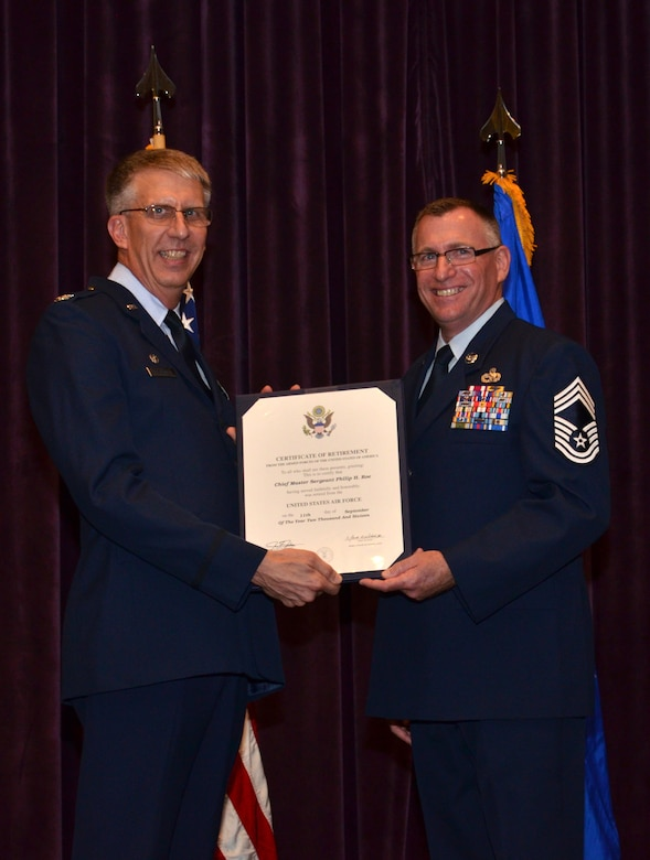 Col. Jeffrey Macrander, 920th Rescue Wing commander (left), presents a certificate of retirement to Chief Master Sgt. Philip Roe, 920th Aircraft Maintenance Squadron chief enlisted manager and superintendent, Sept. 10, 2016 at Patrick Air Force Base, Fla. Roe served in the Air Force for 36 years, the majority of which was spent with the 920th Rescue Wing. (U.S. Air Force photo by 1st Lt. Anna-Marie Wyant)