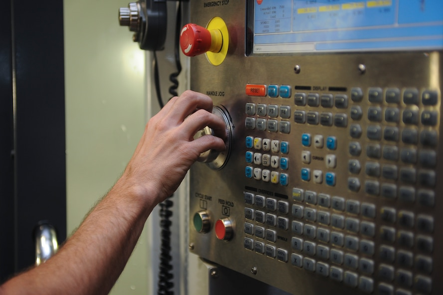 Staff Sgt. Jared Henden, 2nd Maintenance Squadron Fabrication Flight aircraft metals technology journeyman, sets up the Computer Numerical Controlled machine to build a battery tie down bracket at Barksdale Air Force Base, La., Sept. 13, 2016. The CNC is programmed plans to build different parts so Airmen don't have to create them manually. (U.S. Air Force photo/Airman 1st Class Stuart Bright)